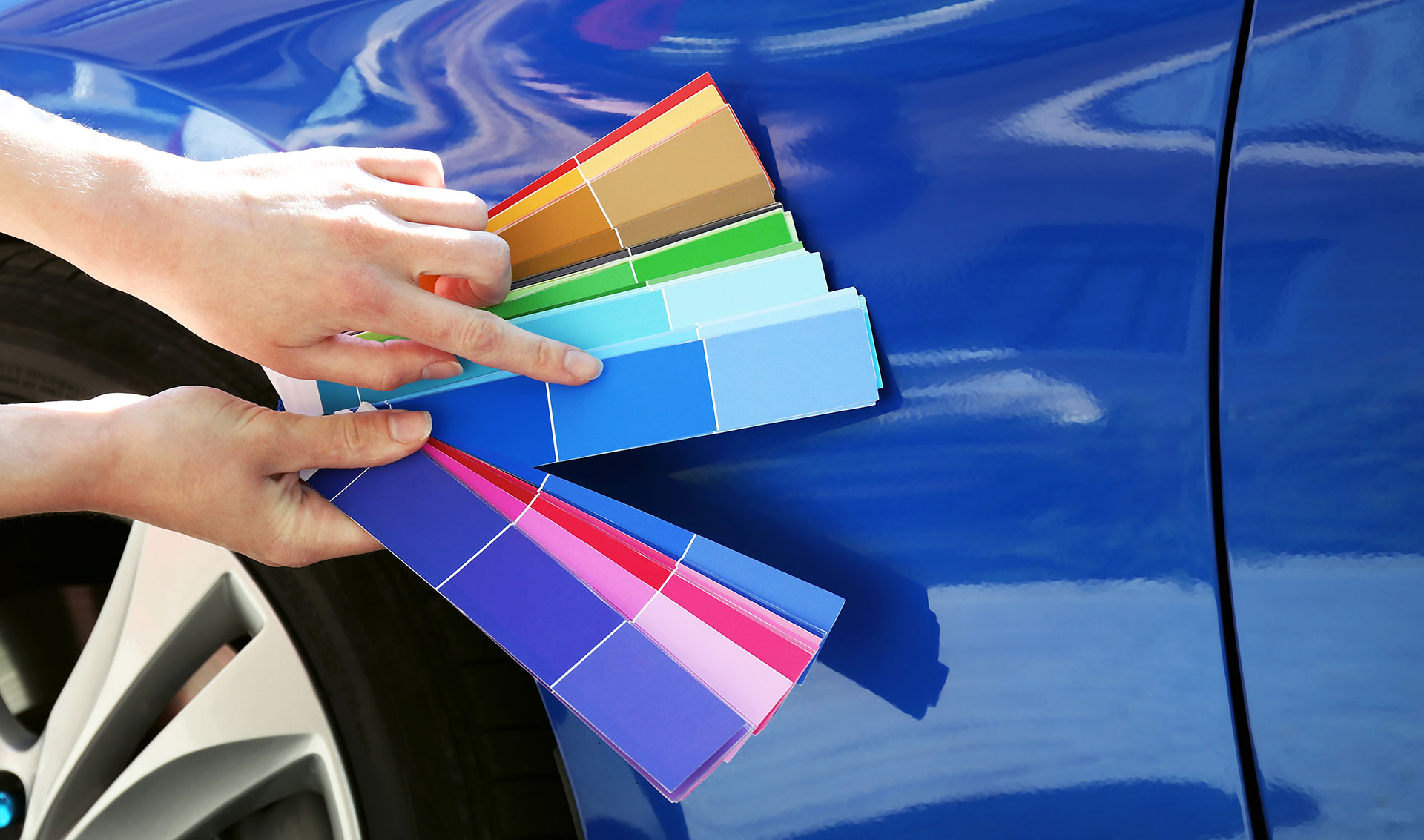 Holding various color swatches against a blue car.