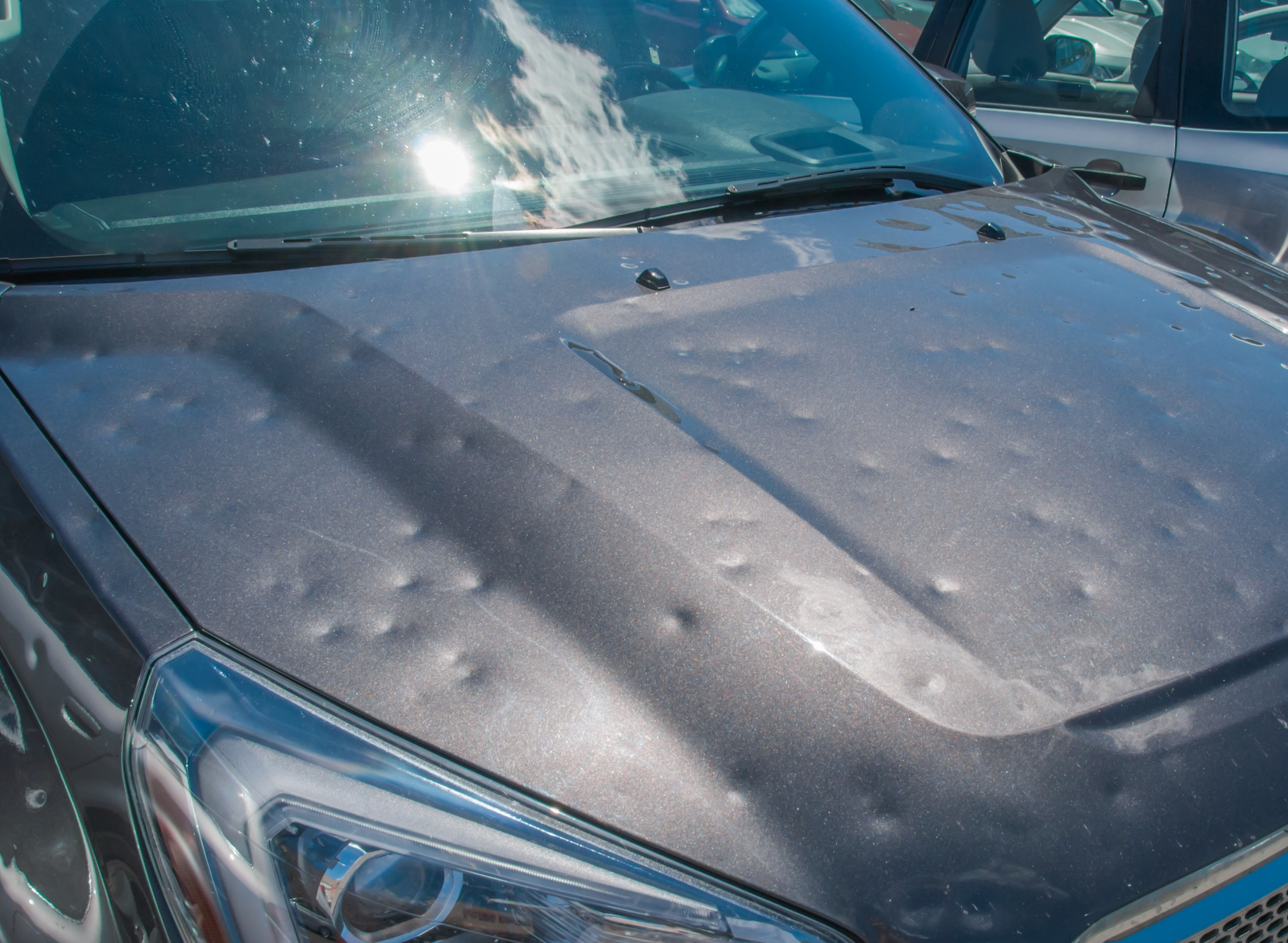Hood of a car riddled with dents.
