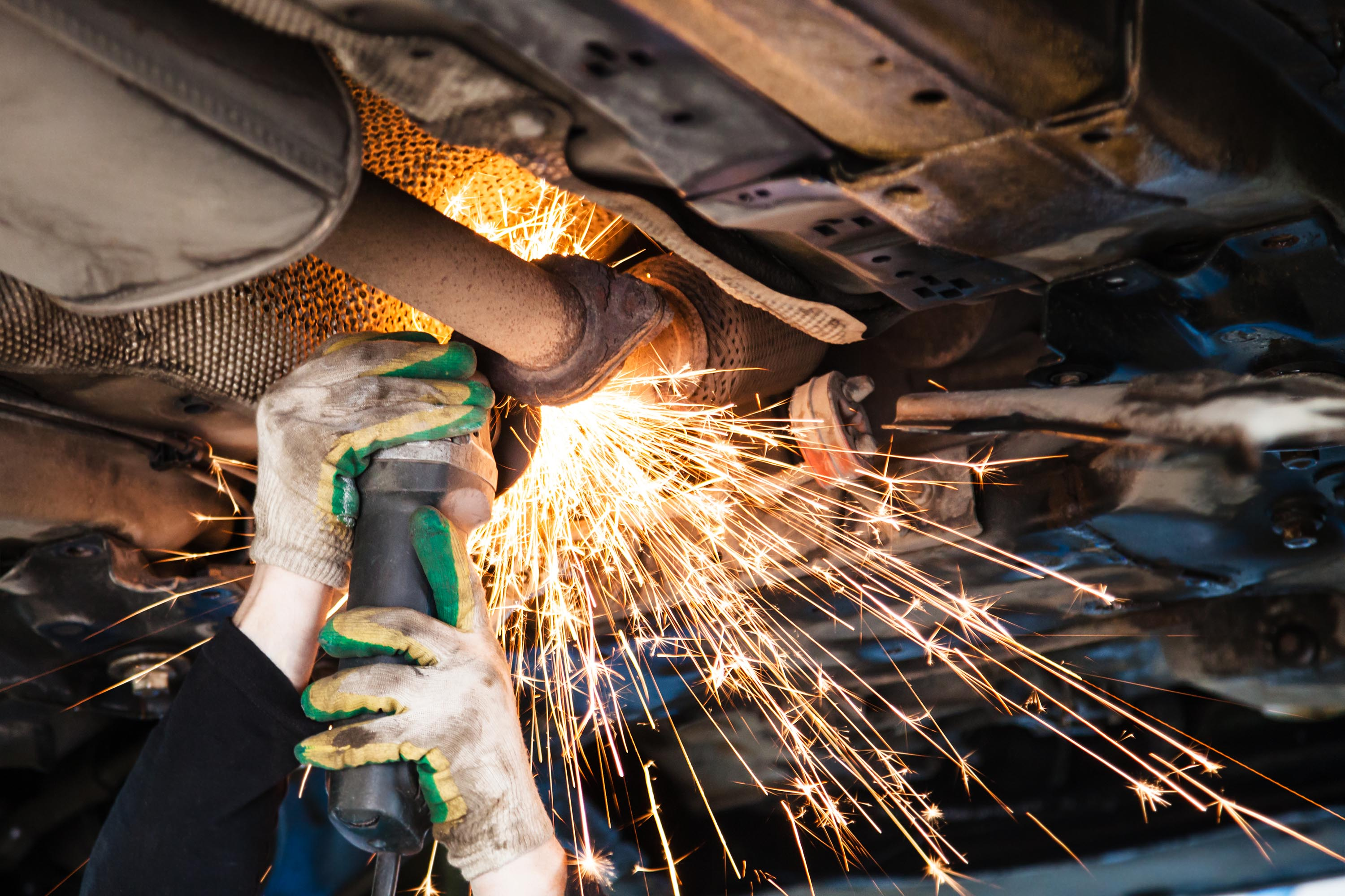 An image of someone using an angle grinder on the underside of a car.