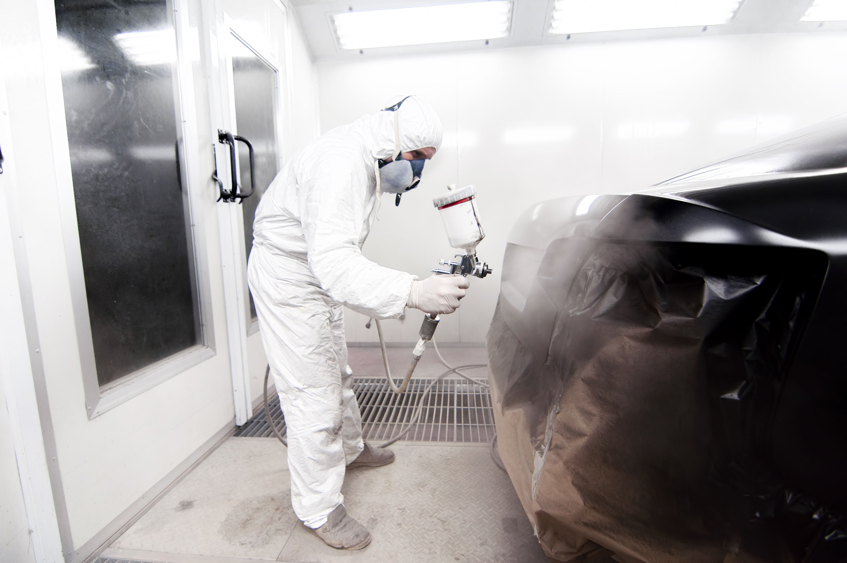 A image of someone painting a car black.