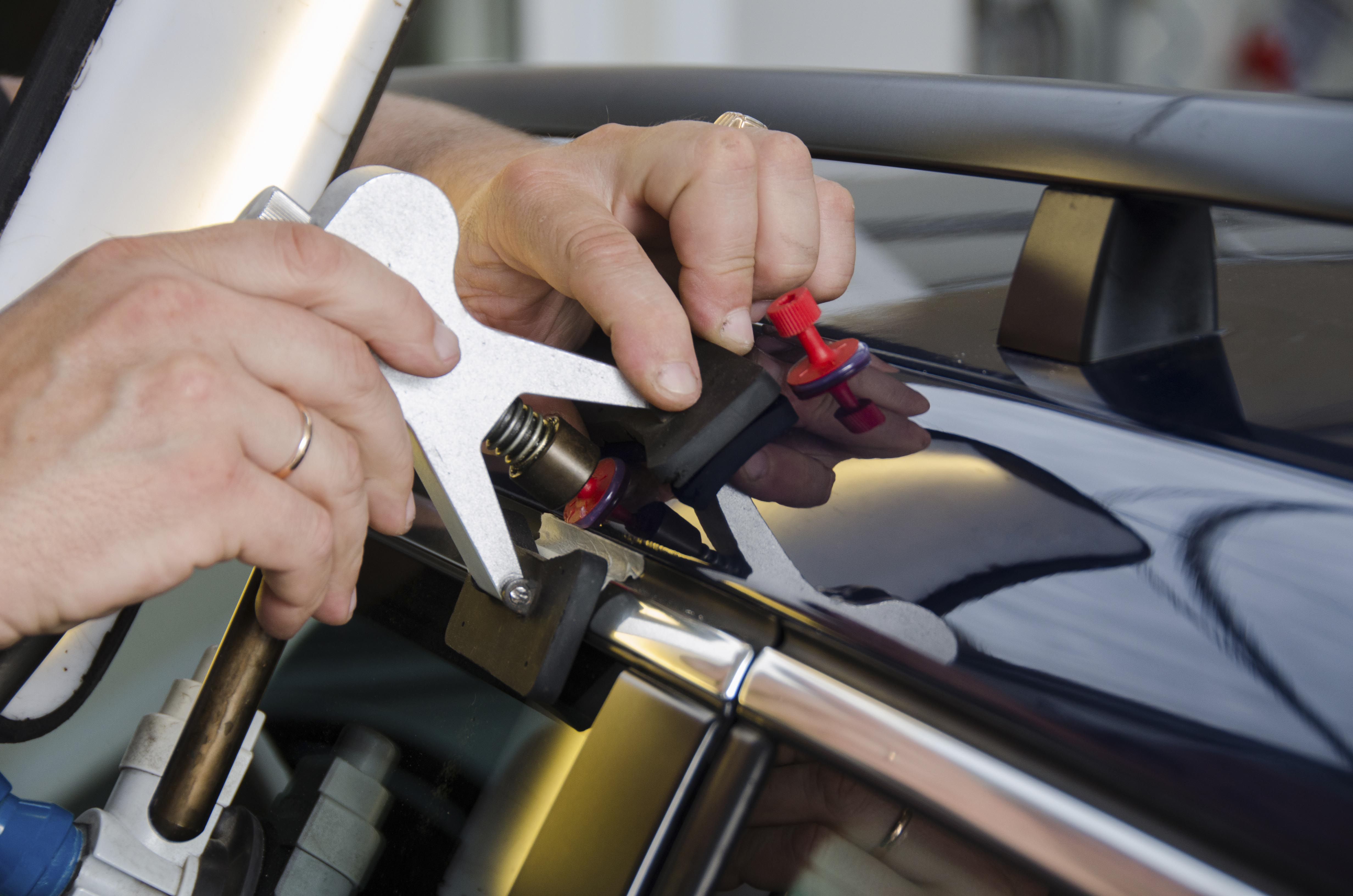 An image of someone using tools for removing dents from vehicles.